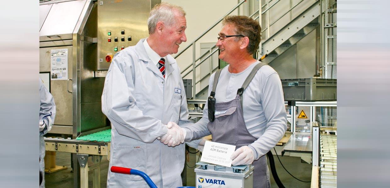 Mitarbeiter Jürgen Ahnert (r.) übergibt die 40millionste bei Johnson Controls Zwickau produzierte AGM-Batterie an Werkleiter Matthias Horn.