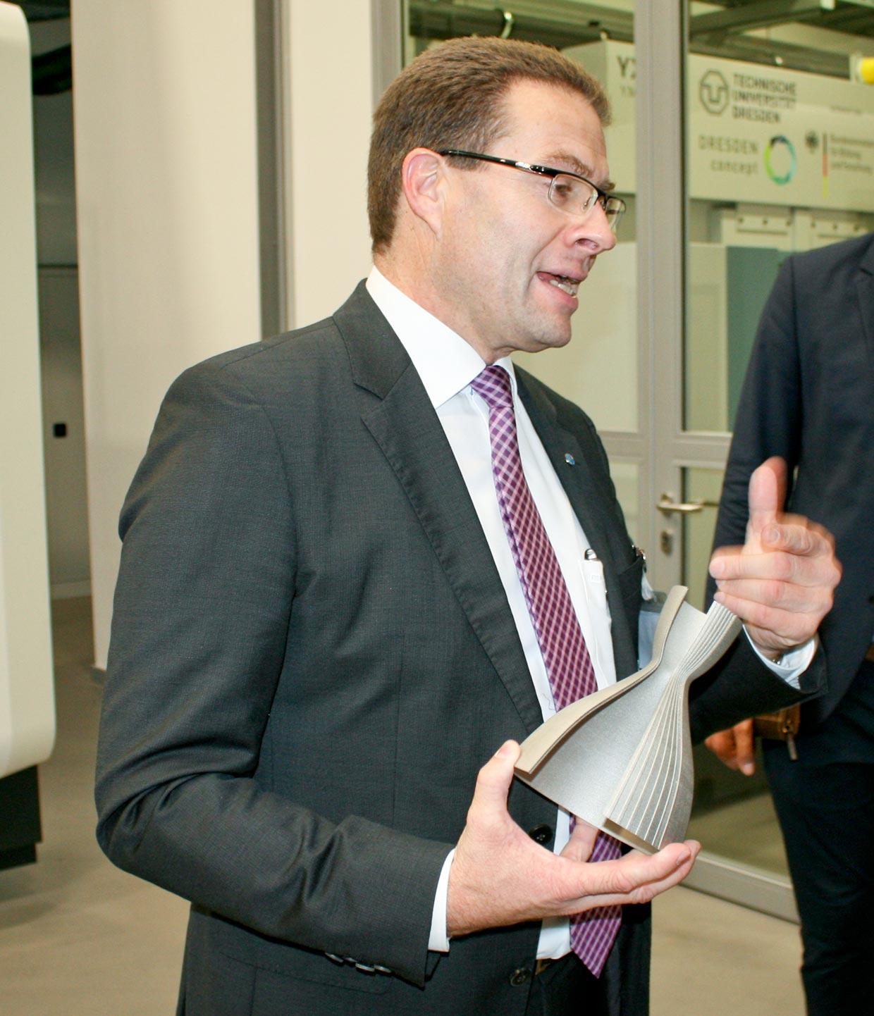 Prof. Christoph Leyens stellt eine additiv gefertigte Brennkammer mit integrierten Kühlkanälen für eine Raumfahrtanwendung vor.