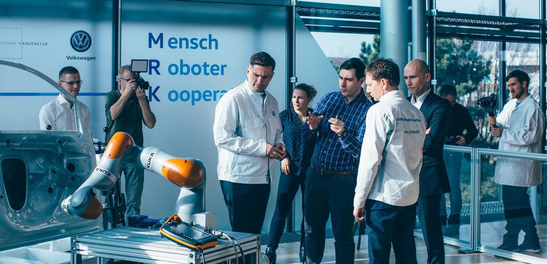 Der sächsische Ministerpräsident Michael Kretschmer probiert in der Gläsernen VW-Manufaktur in Dresden die neue Sensorjacke von Wandelbots. Ziel ist die verbesserte Mensch-Roboter-Kollaboration.