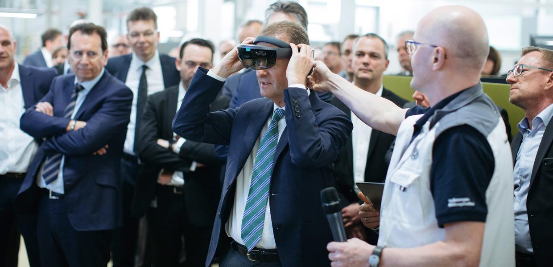 Dr. Herbert Diess, Vorstandsvorsitzender der Marke Volkswagen, mit einer von Auszubildenden programmierten Datenbrille zum Training der Teilepositionierung im Karosseriebau.