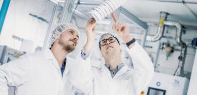 Im Carbonfaser-Technikum: Die RCCF-Wissenschaftler Benjamin Richter und Daniel Wolz begutachten vor der Carbonisierungslinie die entstandene Faser.