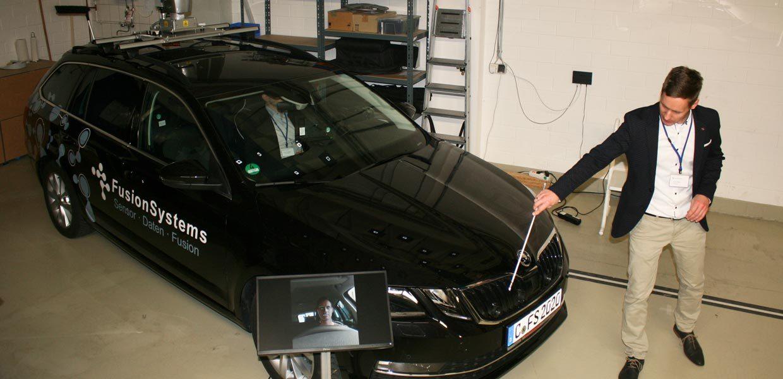 Oliver Fohl stellte das Sensorfahrzeug von FusionSystems vor, das dank seiner technischen Ausstattung sein Umfeld komplett erfassen kann. Dafür sorgen u.a. zusätzliche Kameras im Frontgrill sowie ein 360-Grad-Laserscanner und eine Kugelkamera auf dem Dach.