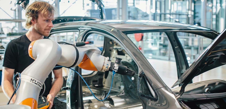 """Im neuen """"Software Development Center Production"""" in der Gläsernen Manufaktur Dresden arbeten IT-Spezialisten an der VW Industrial Cloud. Eine erste Entwicklung ist die Software für die optische Qualitätskontrolle des automatisierten Primer-Auftrages der Tür-Dreiecksscheibe – die Roboter-Anwendung kommt vom Dresdner Startup Wandelbots"""