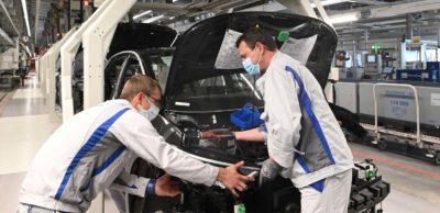 Zwei Mitarbeiter des VW-Werkes Zwickau verbauen das Frontend am ID.3. Zum Wiederanlauf der Produktion wurde ein Maßnahmenkatalog zum Gesundheitsschutz zwischen Unternehmen und Betriebsrat vereinbart, der etwa das Tragen des Mund-Nasen-Schutzes an Arbeitsplätzen mit weniger als 1,5 Meter Abstand zueinander vorsieht.