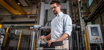 Ressourceneffiziente Sammelbehälter für E-Müllautos: Marcus Hartenstein, Wissenschaftlicher Mitarbeiter an der Professur SLK der TU Chemnitz, prüft die Dicke eines Organoblechs. Das Element für den innovativen Abfallbehälter wurde im MERGE-Zentrum gefertigt.