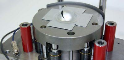 Die Prüfmaschine ist Teil des IWU-Werkstofftesters. In der Maschine drückt ein halbkugelförmiger Stempel das Werkstück bis zu einer definierten Tiefe ein. Die Analyse des Kraft-Weg-Verlaufs erlaubt detaillierte Rückschlüsse auf die Qualität des Materials.