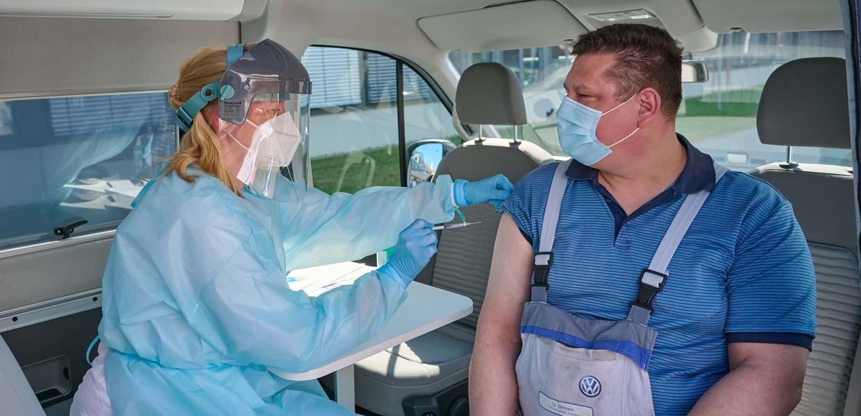 Modellprojekt zur Corona-Impfung: VW-Logistiker Udo Strewe erhält die erste Impfung von Werksärztin Dr. Nicole Walther im neuen Impfmobil in Zwickau.