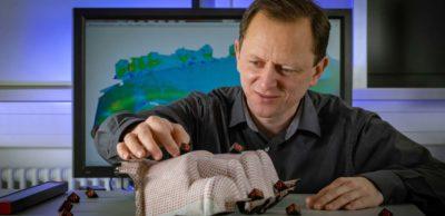 """MERGE-Wissenschaftler Dr. Roman Rinberg platziert Marker auf einer Demonstratorversion der Mikrosandwich-Kartentasche. Eine spezielle 3D-Messtechnik analysiert im MERGE Research Centre """"Lightweight Technologies"""" mithilfe komplexer mathematischer Algorithmen eine 3D-Punktewolke der gescannten Oberfläche."""